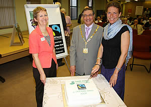 Hannah Reed of the Fairtrade Foundation cuts the celebration cake, watched by Councillor Amrit Mediratta, Chairman of TRDC, and Jane Brading from the Three Rivers Fairtrade Group.