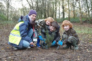 Libby Trustcott (Three Rivers District Council Play Ranger) with some of the children planting trees