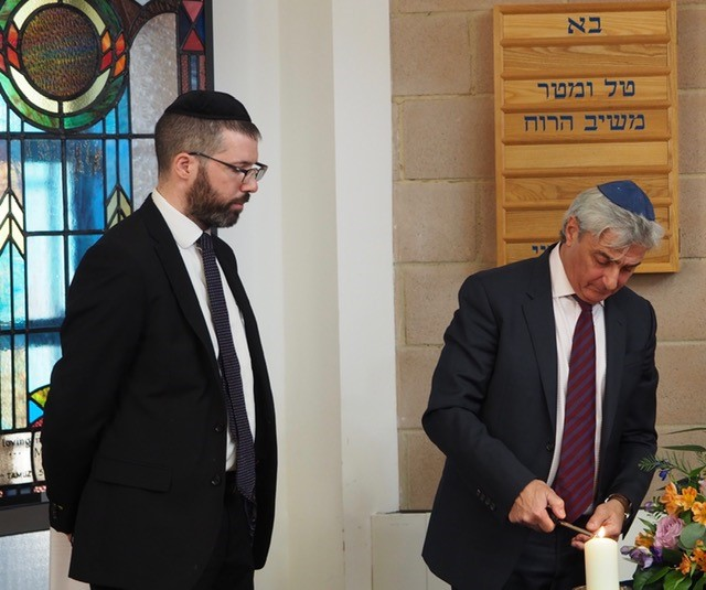 michael-bibring-lights-a-memorial-candle-watched-by-northwood-united-synagogue-s-rabbi-aharon-zerbib.jpg